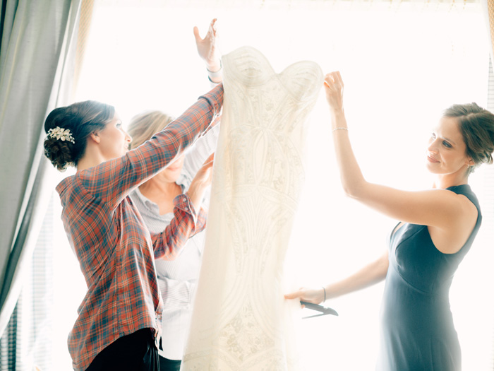 bride removing dress from hanger